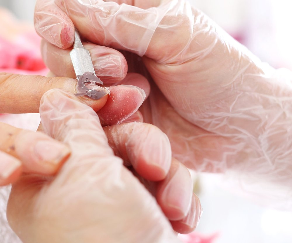 Beautician scratches the nail varnish of the client.