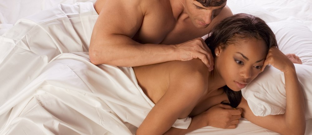 young heterosexual couple in bed. Mid adult Caucasian men in late 30s and young black African-American woman in 20s