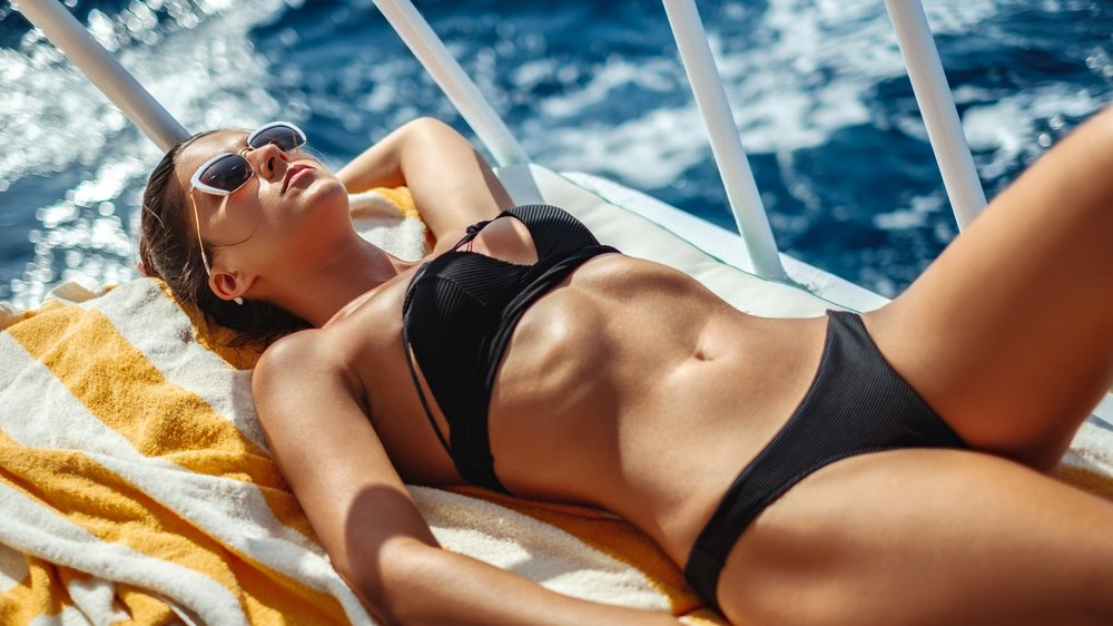 Beautiful girl tanning on a boat deck while sailing on waves