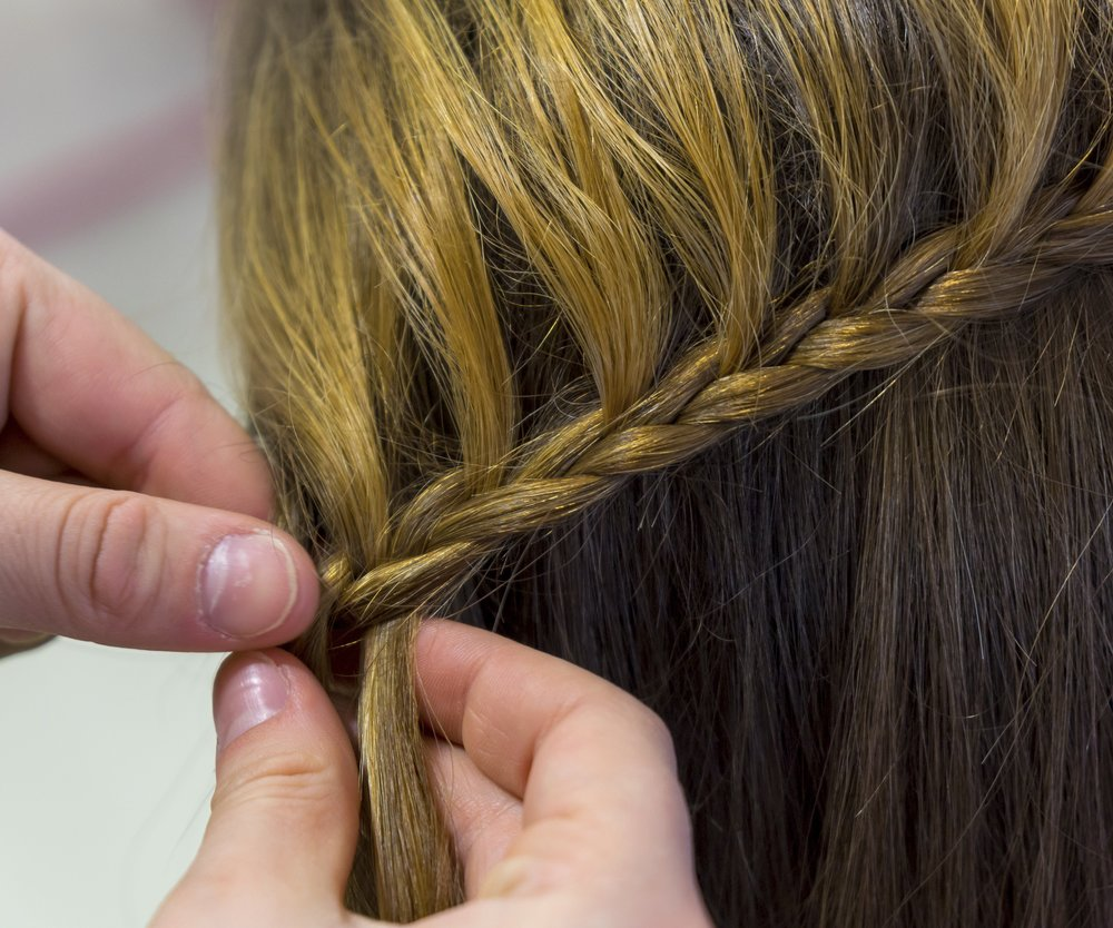 Hairdresser makes braids in beauty salon.