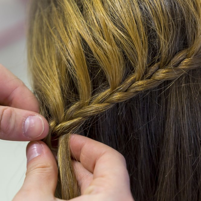 Hairdresser makes braids in beauty salon.