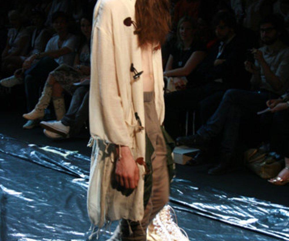 knielanger, beiger Kapuzenmantel mit Fransen zur braunen Hose von Patrick Mohr