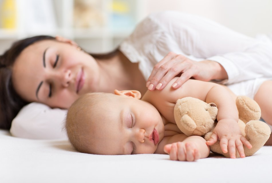 mother and her son baby sleeping together in a bedroom