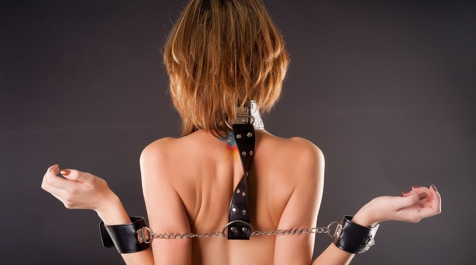 Woman with handcuffs. Bondage concept. Studio shot