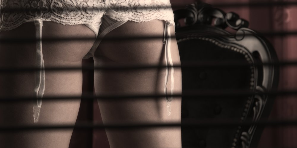 A gorgeous female standing behind blinds wearing lingerie and stockings