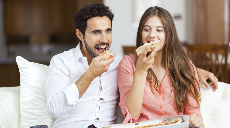 Couple with pizza and TV remote