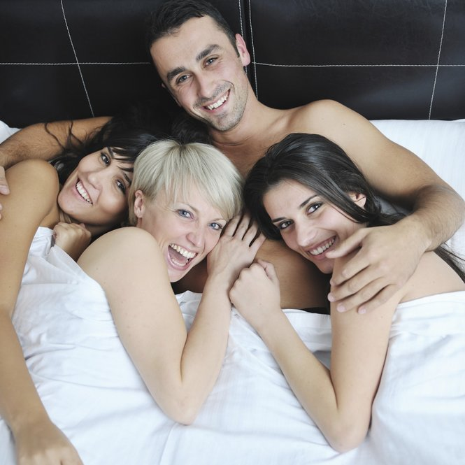 successful Young handsome man lying in bed with three sleeping girls