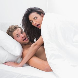 Embarrassed couple surprised in bed