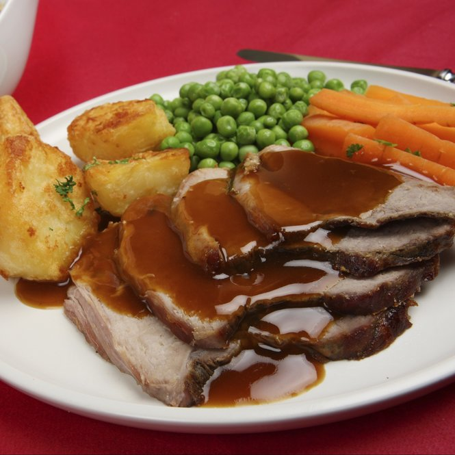 Traditional Sunday roast lamb dinner with gravy