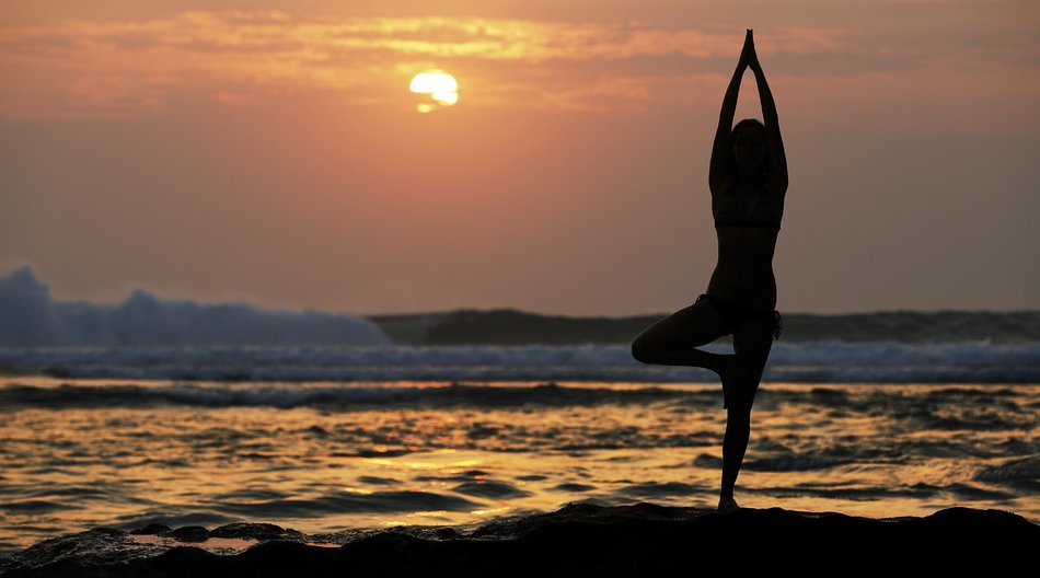 Eine Frau macht Pilates im Sonnenuntergang