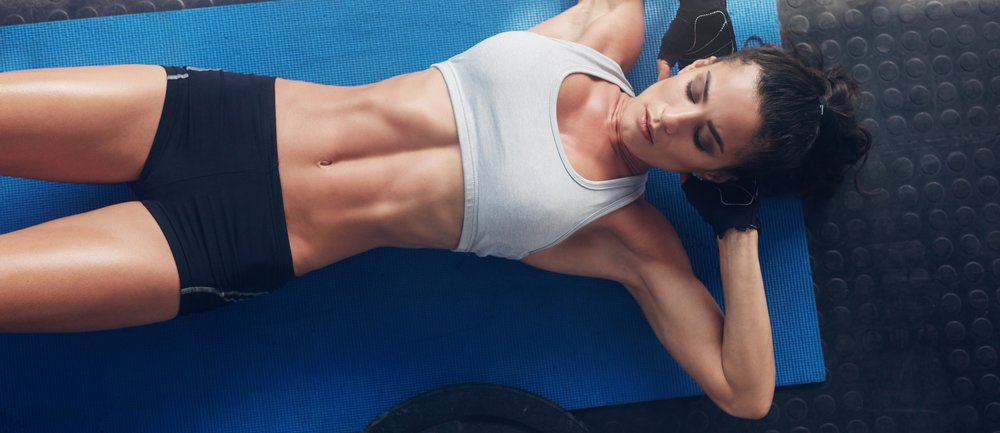 Top view of woman exercising on yoga mat. Fitness female lying on exercise mat with her hands behind head at gym.