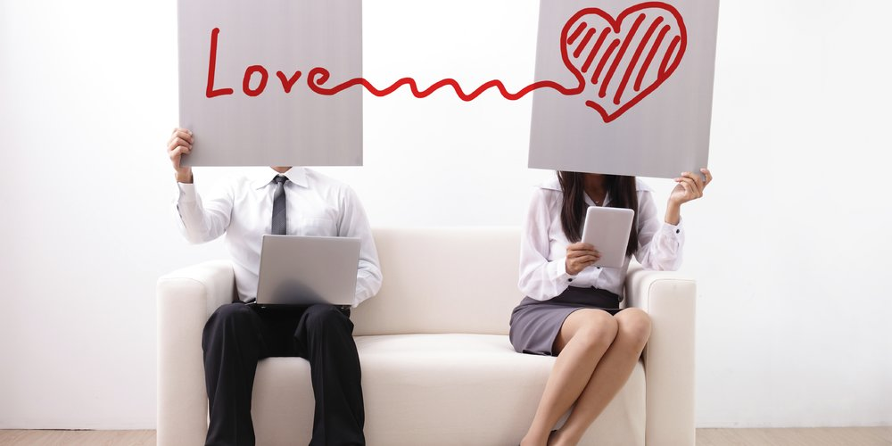 Find ture love on internet - man and woman using computer and digital tablet on sofa