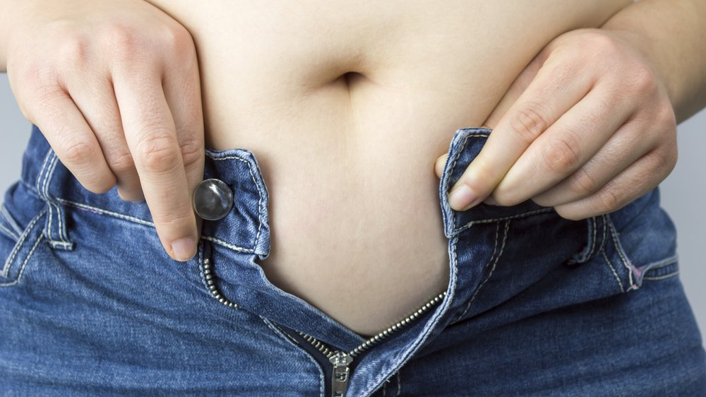 Cropped mid section of an obese woman trying to close the buttons of her jeans against a white background