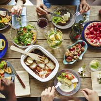 People having a rich dinner with fresh vegetables and homemade meal