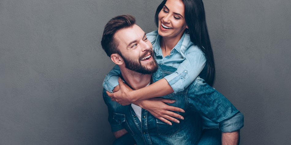 Handsome young man piggybacking beautiful woman and smiling while standing against grey background