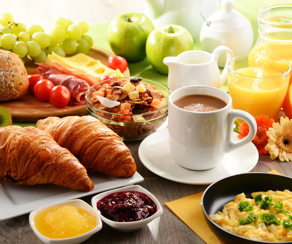 Breakfast served with coffee, orange juice, egg, rolls and honey. Balanced diet.