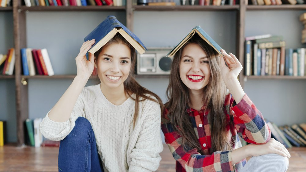 Hipster girls hiding under book.
