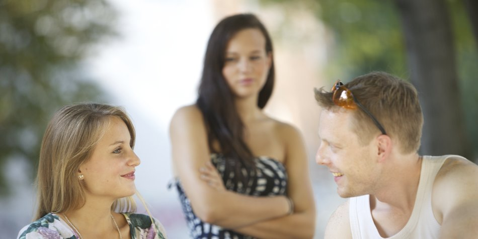 Jealous woman looks at cheerful couple.