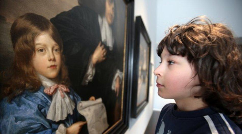 """Der Schüler Emil Kriegeskorte (r) vor dem Gemälde """"Johannes Cunaeus mit Sohn Philippus"""" von Jan Mijtens aus dem Jahr 1663."""