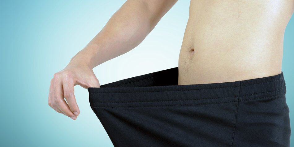 Young man wearing big loose shorts - weight loss concept
