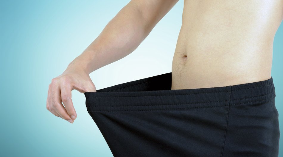 Young man wearing big loose shorts - weight loss concept