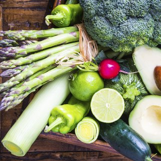 Organic vegetables on rustic dark wood background.Vegan food concept. Green veggies.