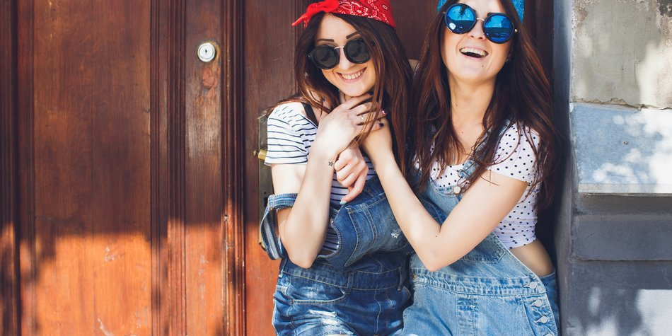 Beautiful young brunette twins sisters, in stylish sunglasses, hugging and laughing. Having fun time together. Wearing denim overalls bright bandanas, posing in front of old doors. Outdoors. Summer day. Copy space.