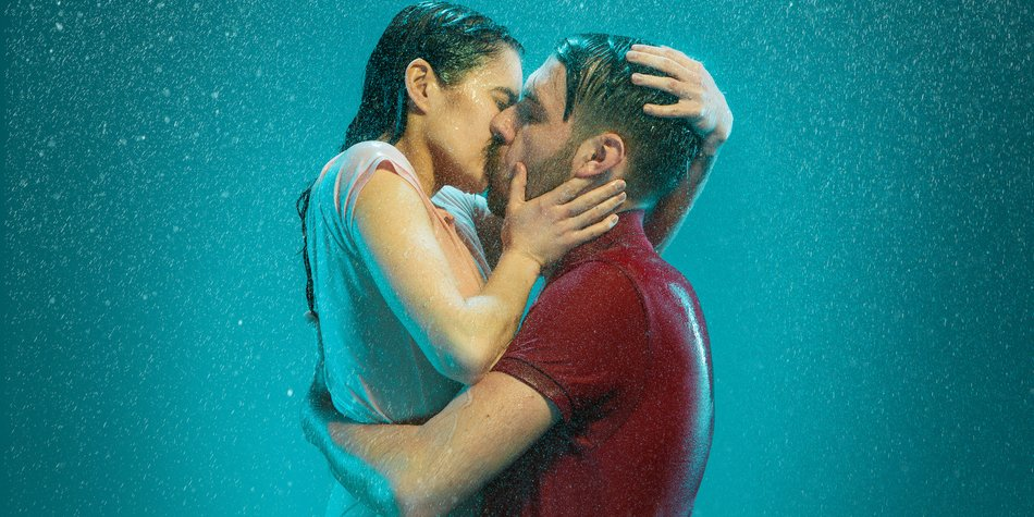 The loving couple kissing in the rain on a turquoise background