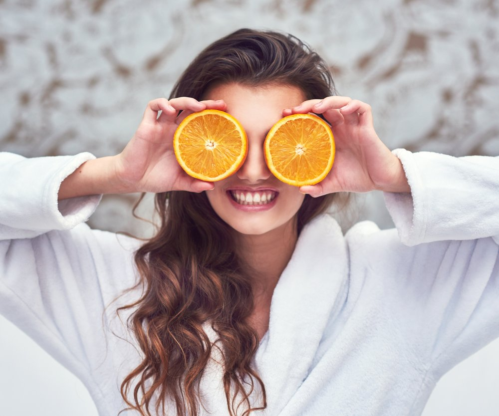 Shot of an attractive young woman holding up orange halves