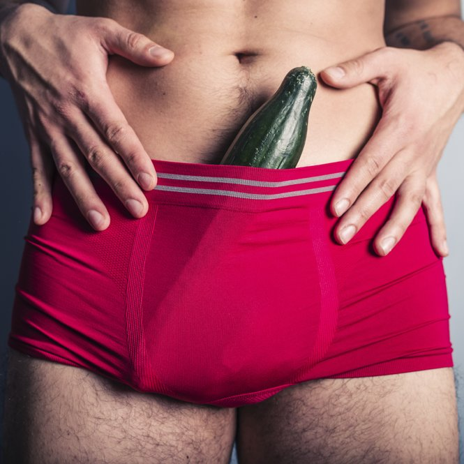 A young man has stuffed a large cucumber down his underpants
