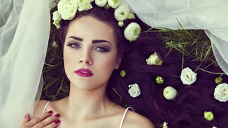 Bride with natural flowers in hair lying on grass