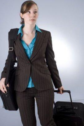 brünette Frau in Businesskleidung trägt eine Laptoptasche und einen Koffe und schaut besorgt
