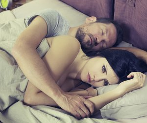 Unhappy sad woman in bed with sleeping boyfriend depressed