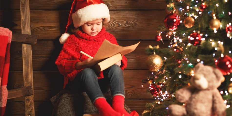 happy child girl writes letter to Santa Claus at the Christmas tree in the evening