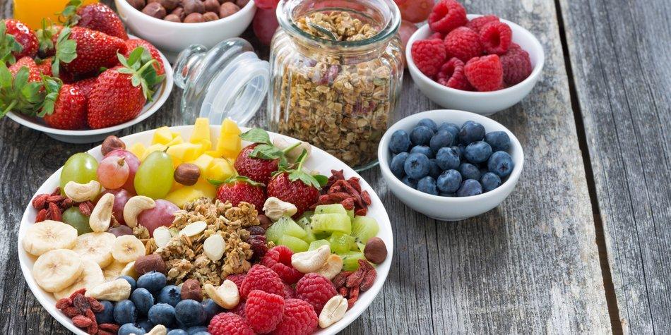 ingredients for a healthy breakfast - berries, fruit, muesli and wooden background, top view, horizontal