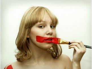 Frau, die sich mit einem breiten Pinsel einen dicken roten Streifen über den Mund malt