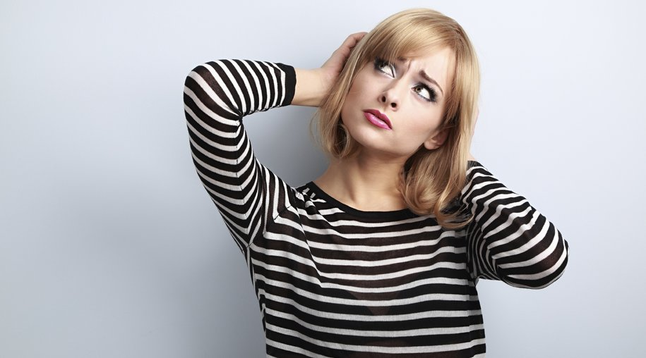 Annoyed unhappy thinking young woman looking up on blue background