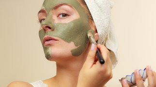 Skin care. Woman applying with brush clay mud mask to her face. Girl taking care of oily complexion. Beauty treatment.