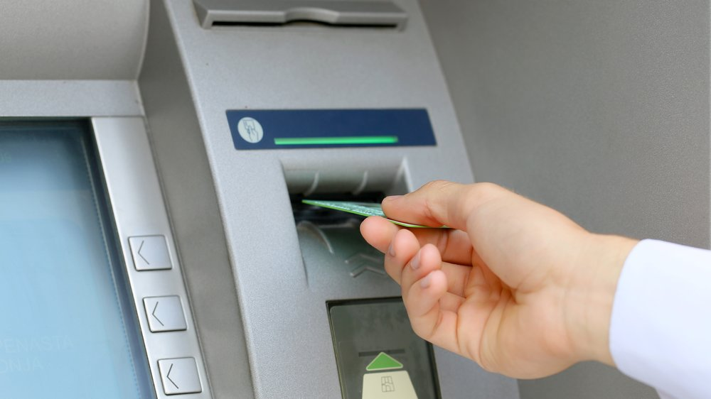 man hand inserting credit card to ATM
