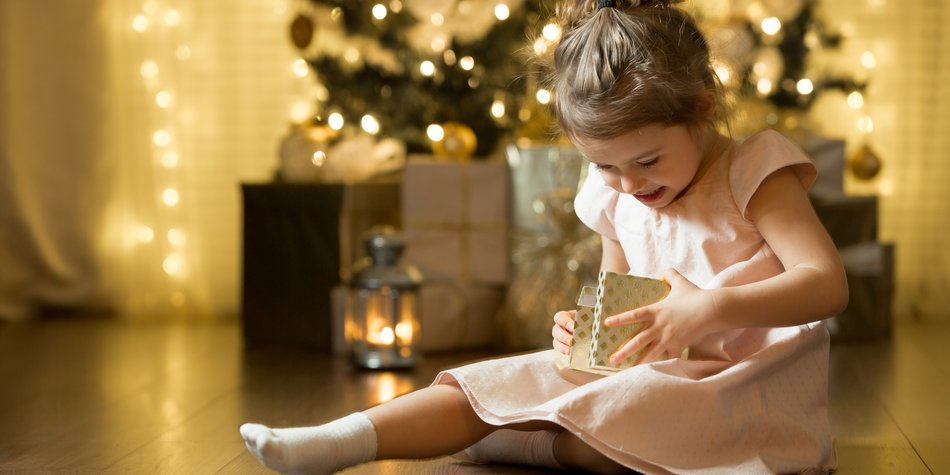 Excited curious little girl smiling, opening christmas gifts. Beautifully decorated christmas tree and house with lights and lantern.