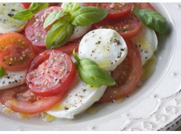 Salat mit Tomaten und Mozzarella garniert mit Basilikum