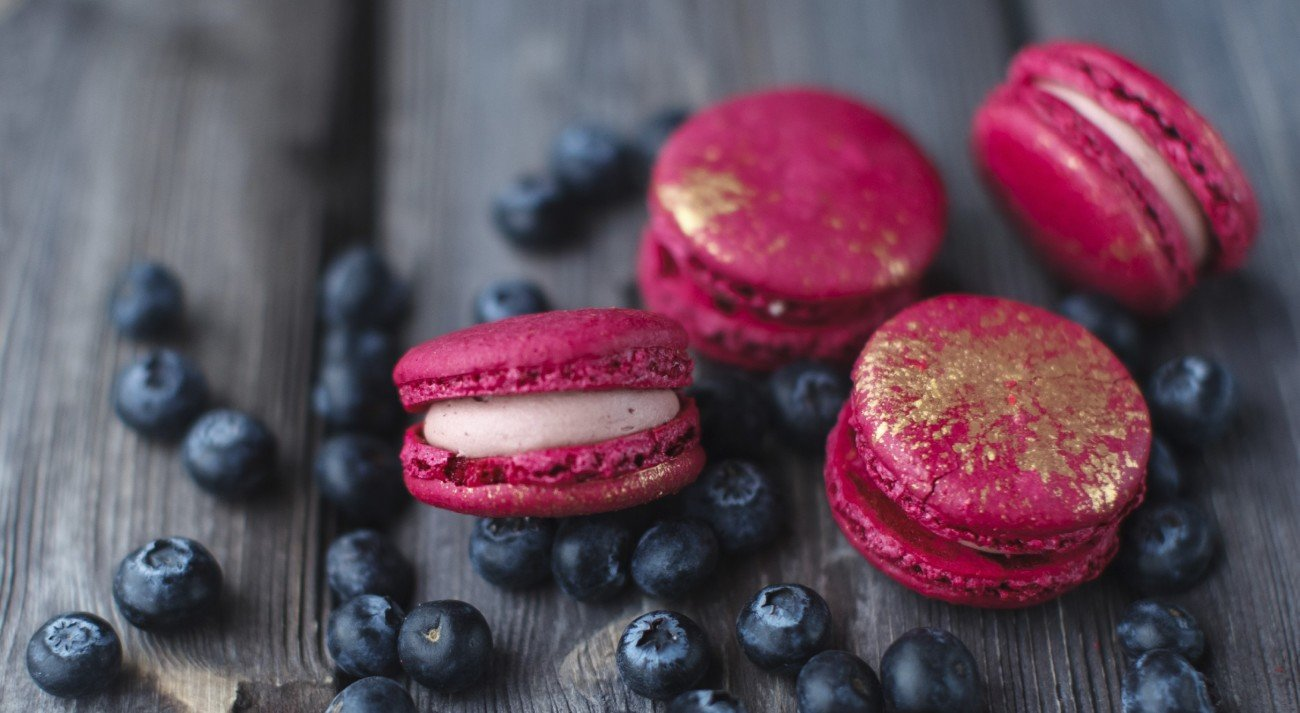 fresh macaroons and ripe blackberry on a wooden background