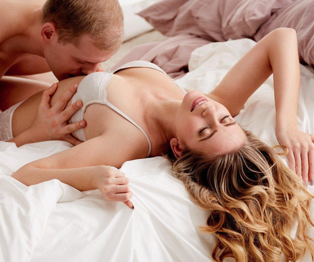 Mann küsst Frau im Bett