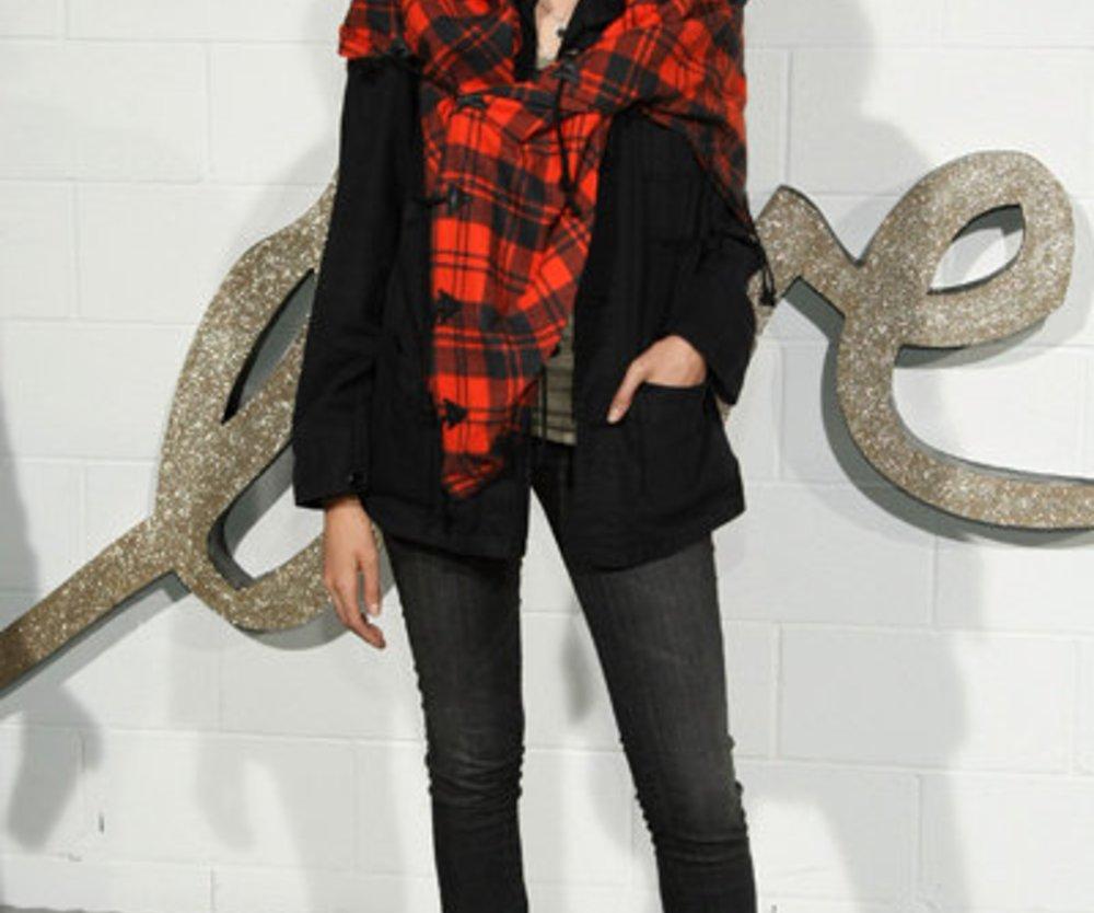 Model Agyness Dean trägt eine Röhrenjeans, Turnschuhe und eine weite Jacke mit Halstuch im Boyfriend-Look