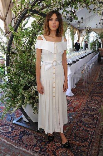 Alexa Chung in einem weißen Retrokleid mit Plisseerock und Perlenknöpfen