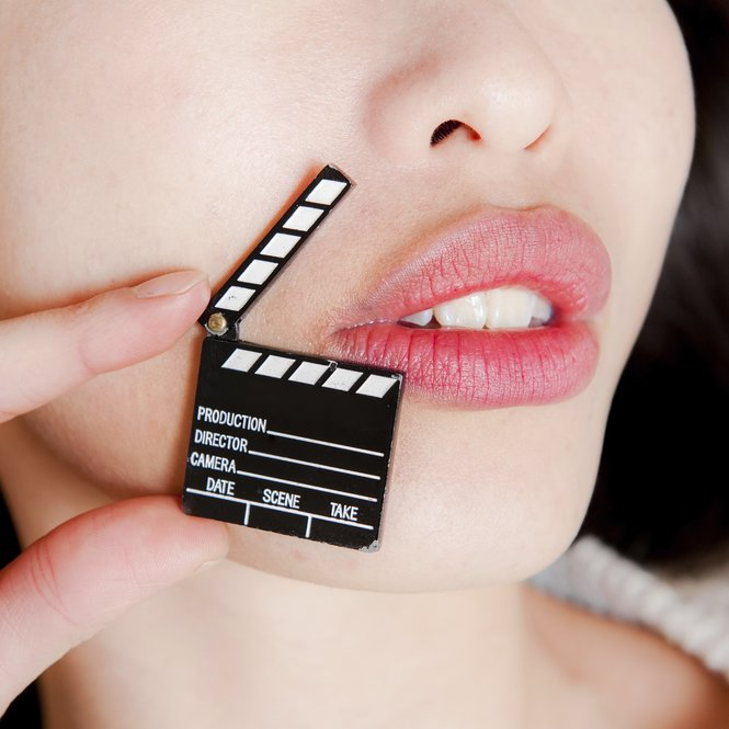 Face detail of sensual woman lips, no eyes, with hand holding little movie clapper board