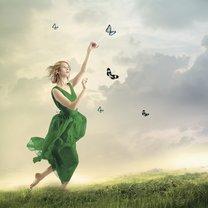 Beautiful girl in a green dress following butterflies on a mountain