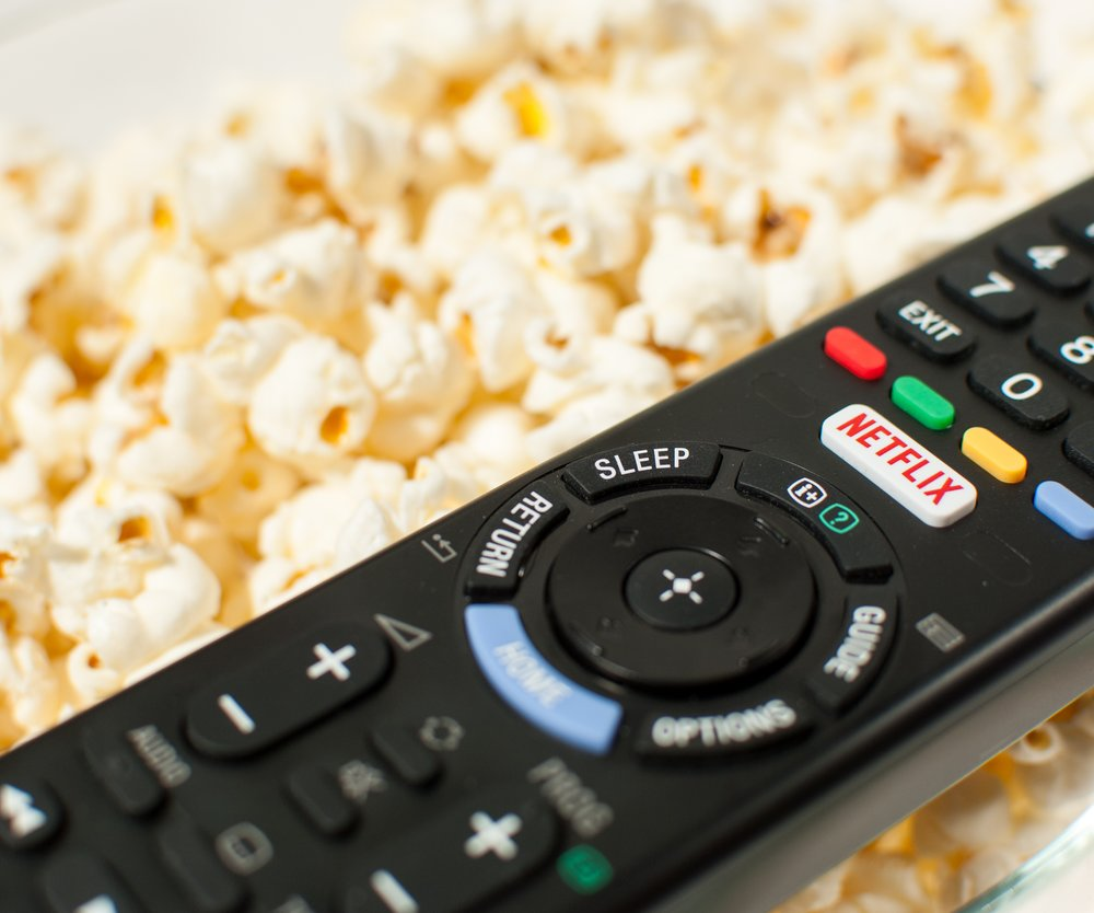 Zagreb, Croatia - March 5, 2016: Remote control smart TV with Netflix button with popcorn in the background.