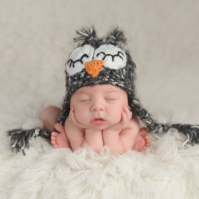 Three week old newborn baby boy wearing a crocheted owl hat. He's in a cute, curled up, chin on hands pose and sleeping on a white flokati rug.