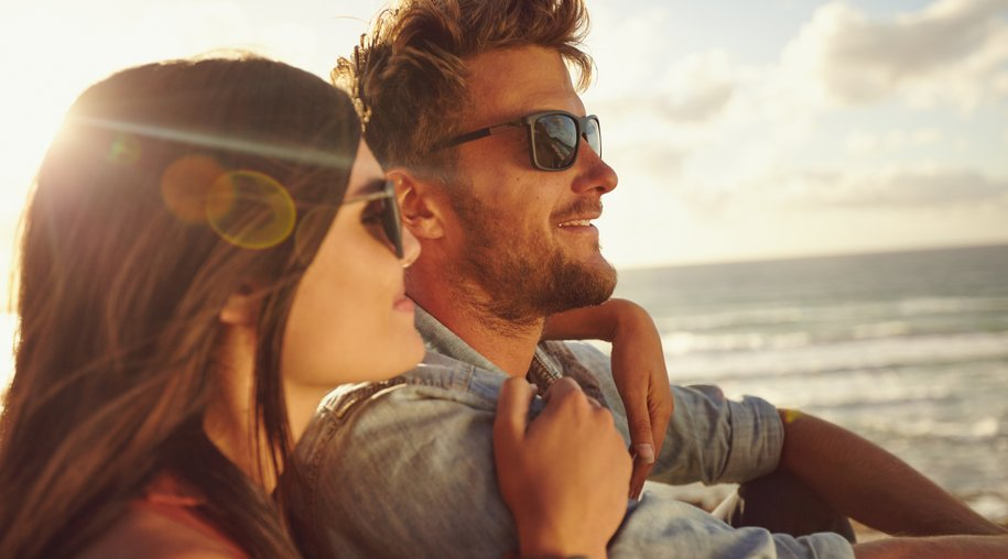 Romantic young couple together outdoors on a summer day. Caucasian couple enjoying the beach view.